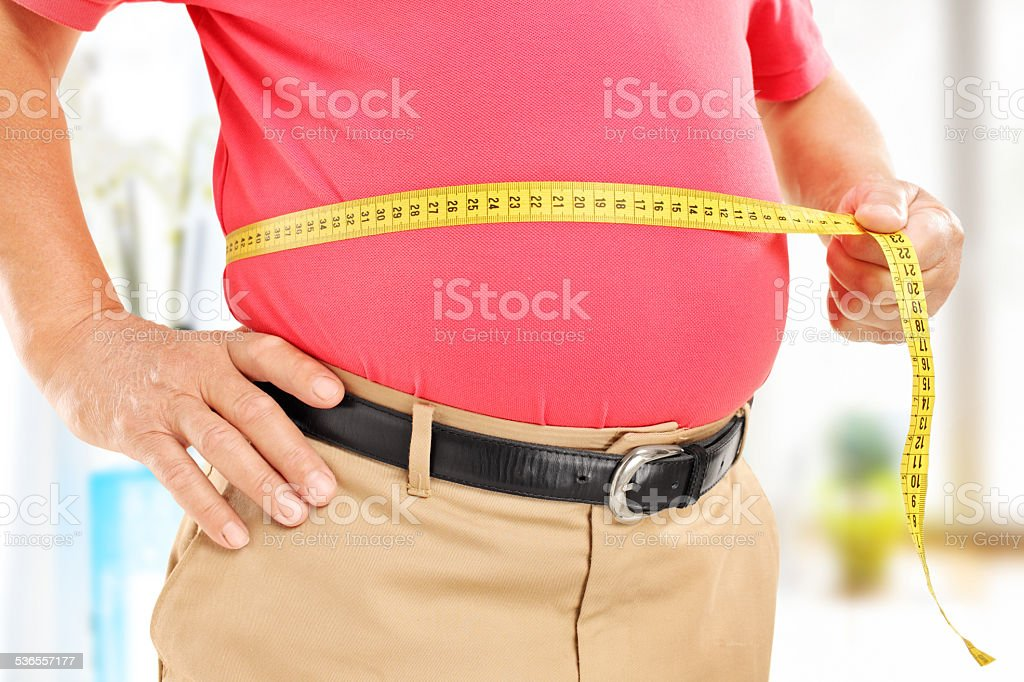 Close-up on a man measuring his belly stock photo
