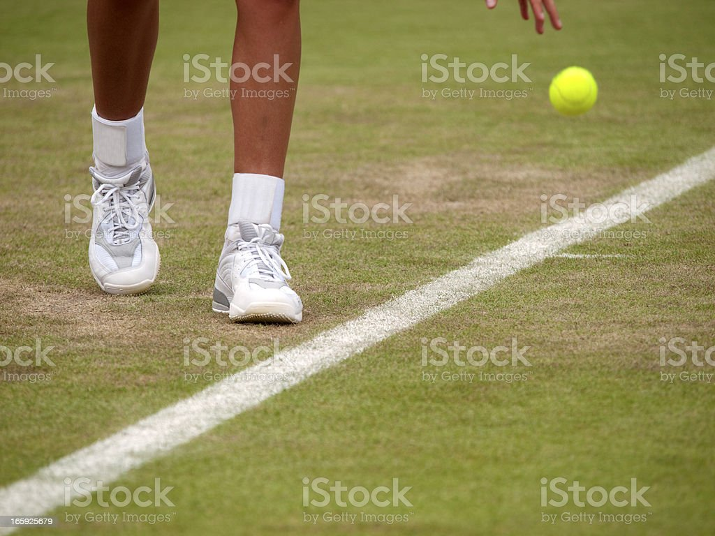 Close-up on a tennis player's feet as they prepare to serve royalty-free stock photo