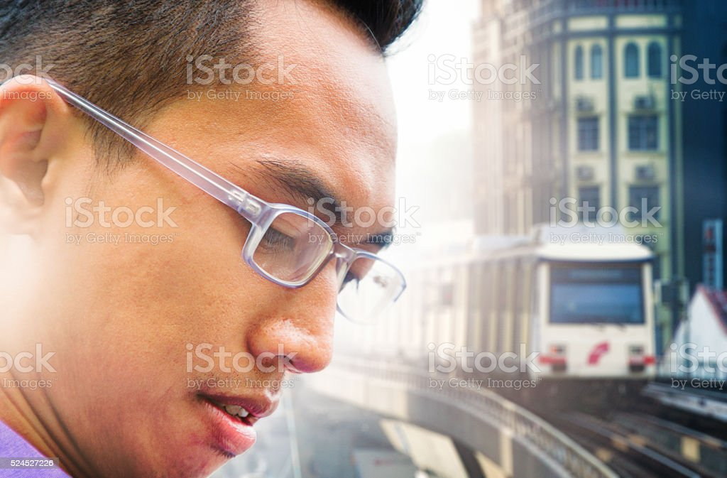 Close-up on Asian male profile waiting for monorail stock photo