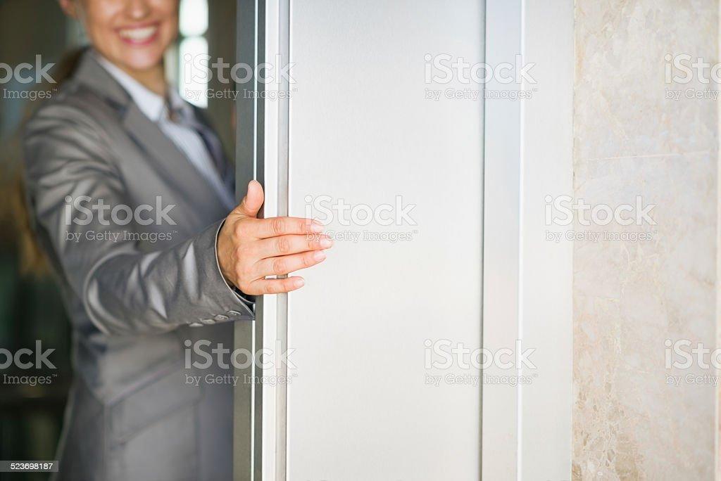 closeup on business woman hand holding elevator door stock photo
