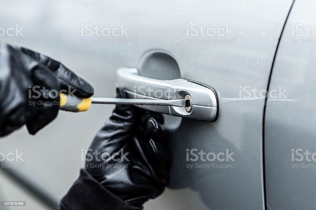 Closeup on car thief hands trying to steal a vehicle stock photo