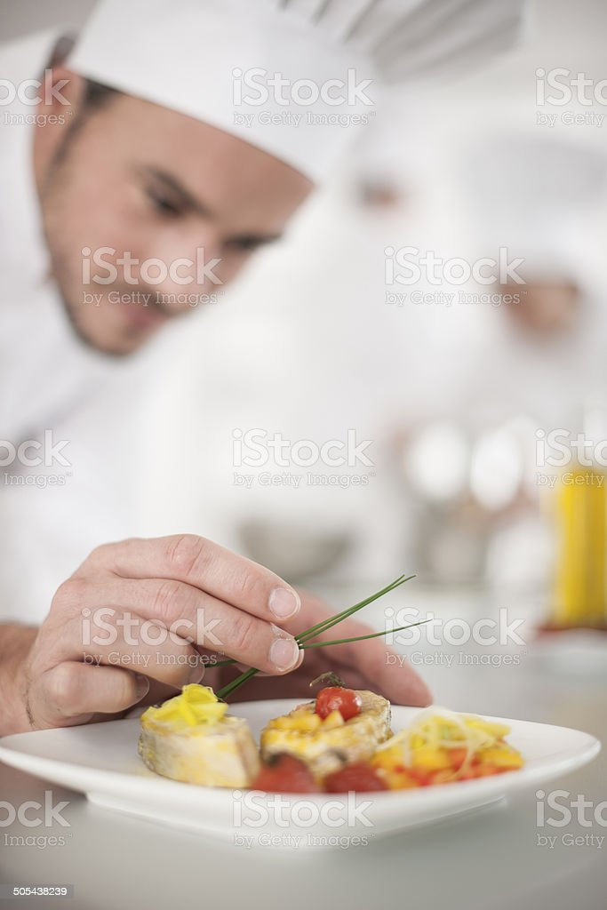 closeup on chef's hands garnishing a plate stock photo