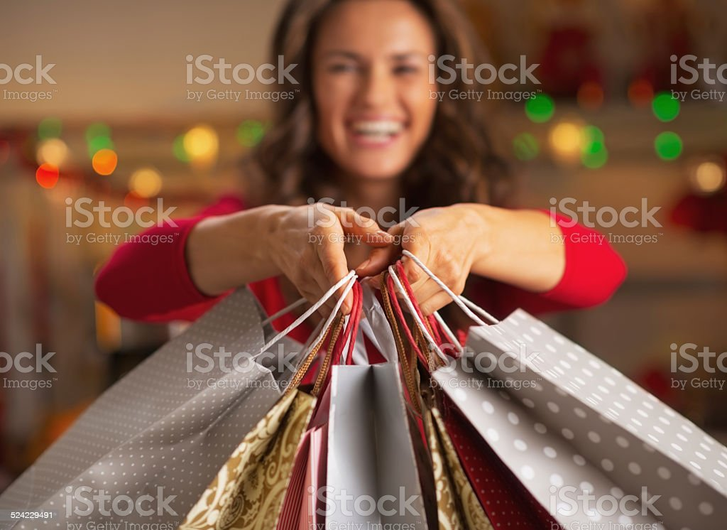 Closeup on christmas shopping bags in hand of smiling woman stock photo