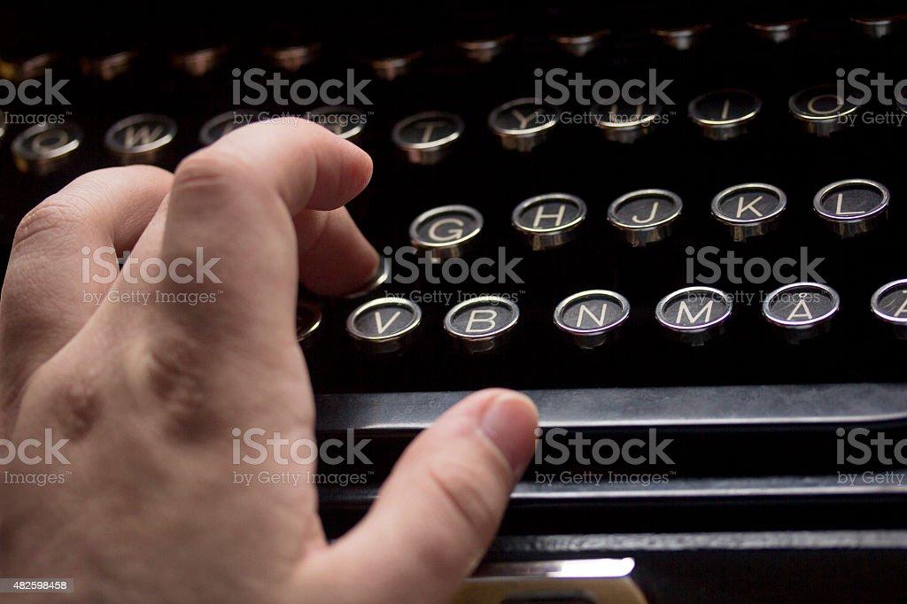 Closeup on hand writing on old vintage typewriter keyboard stock photo