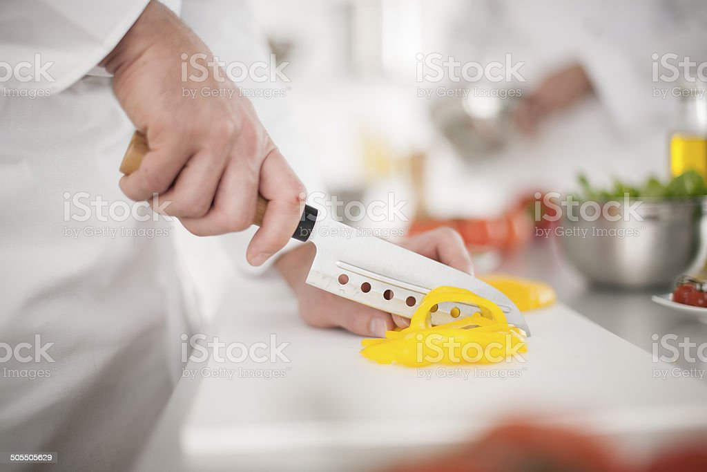 closeup on hands cutting yellow pepper in professional kitchen stock photo