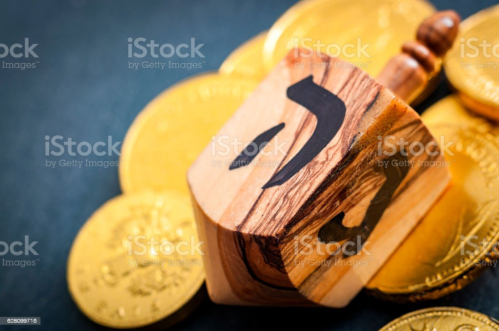 Closeup on Hanukkah dreidel and gold coins with copyspace stock photo
