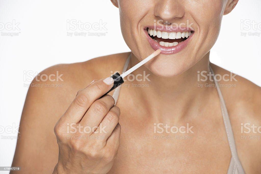 closeup on happy young woman applying lip gloss stock photo