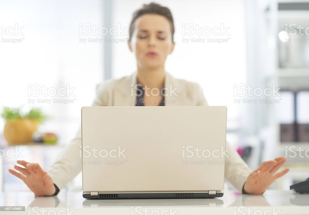 closeup on laptop and relaxing business woman in background stock photo
