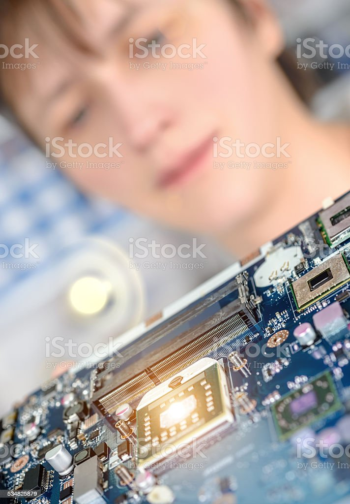 Closeup on motherboard observed by a female tech stock photo