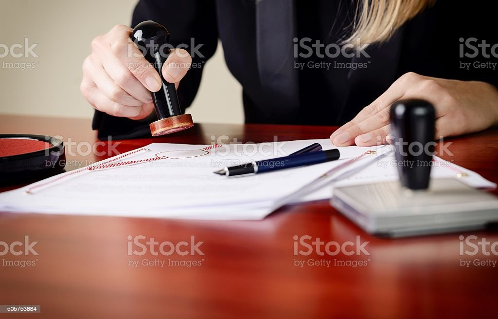 Closeup on notary's public hands stamping document. stock photo