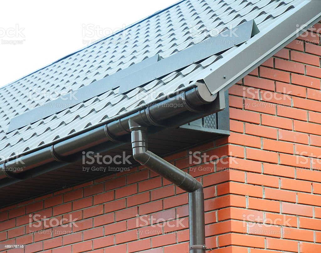 Closeup on rain gutter system and roof snow protection stock photo