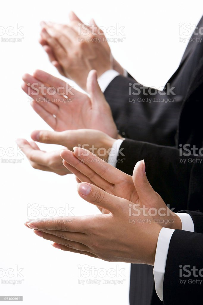 Close-up on the hands clapping of 3 formally dressed people stock photo