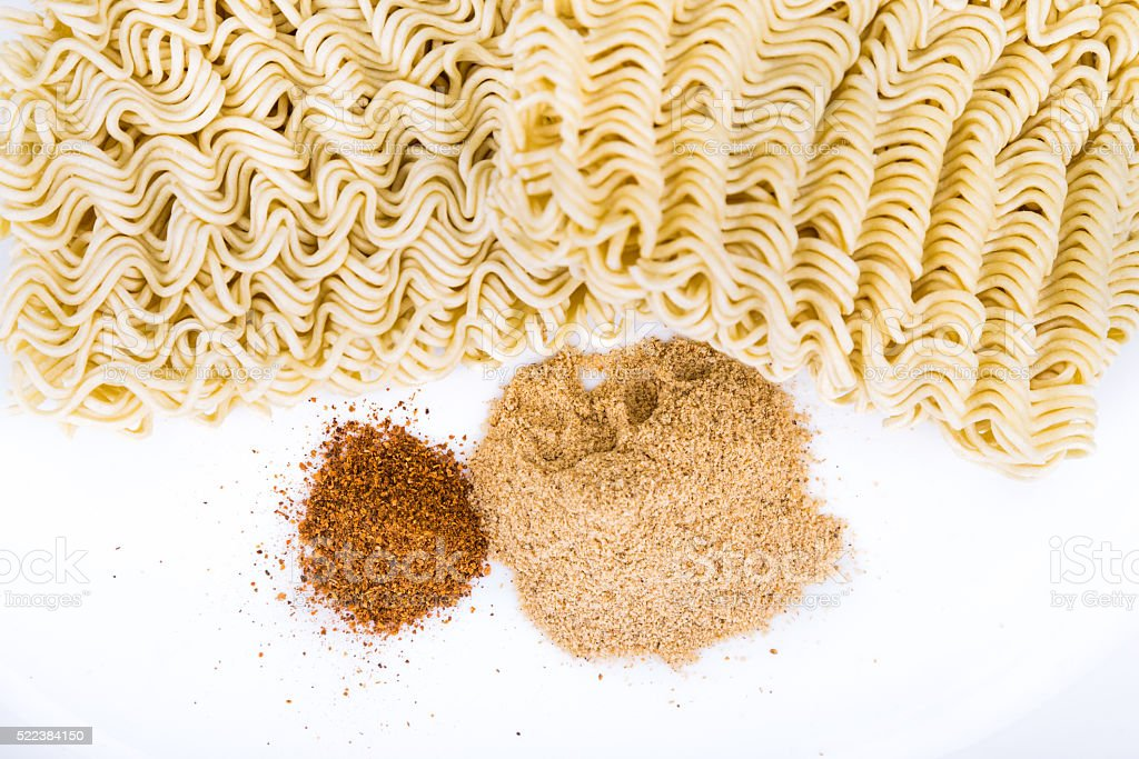 Closeup on unhealthy flavoring powder with uncooked instant nood stock photo
