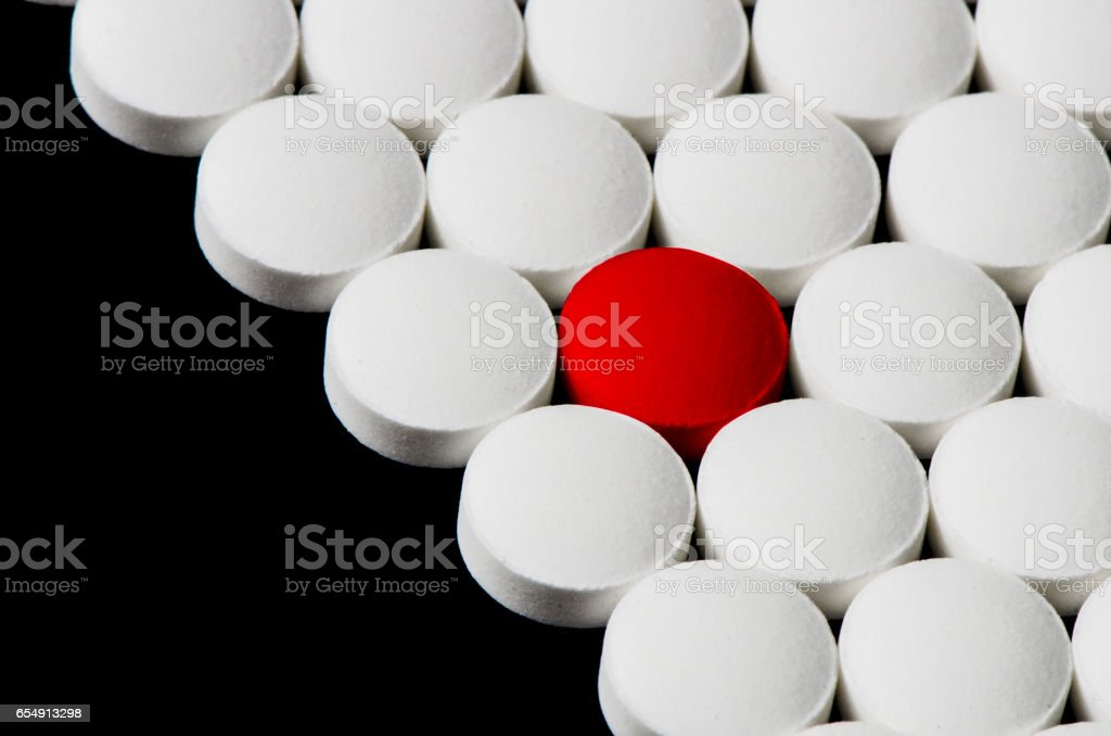 Closeup on white pills with red highlighted stock photo