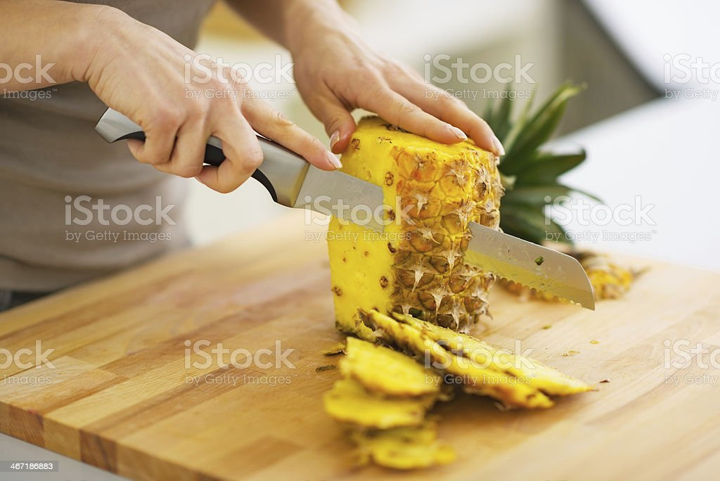closeup on woman cutting pineapple stock photo