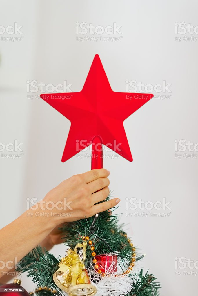 closeup on woman hand decorating christmas tree with topper stock photo