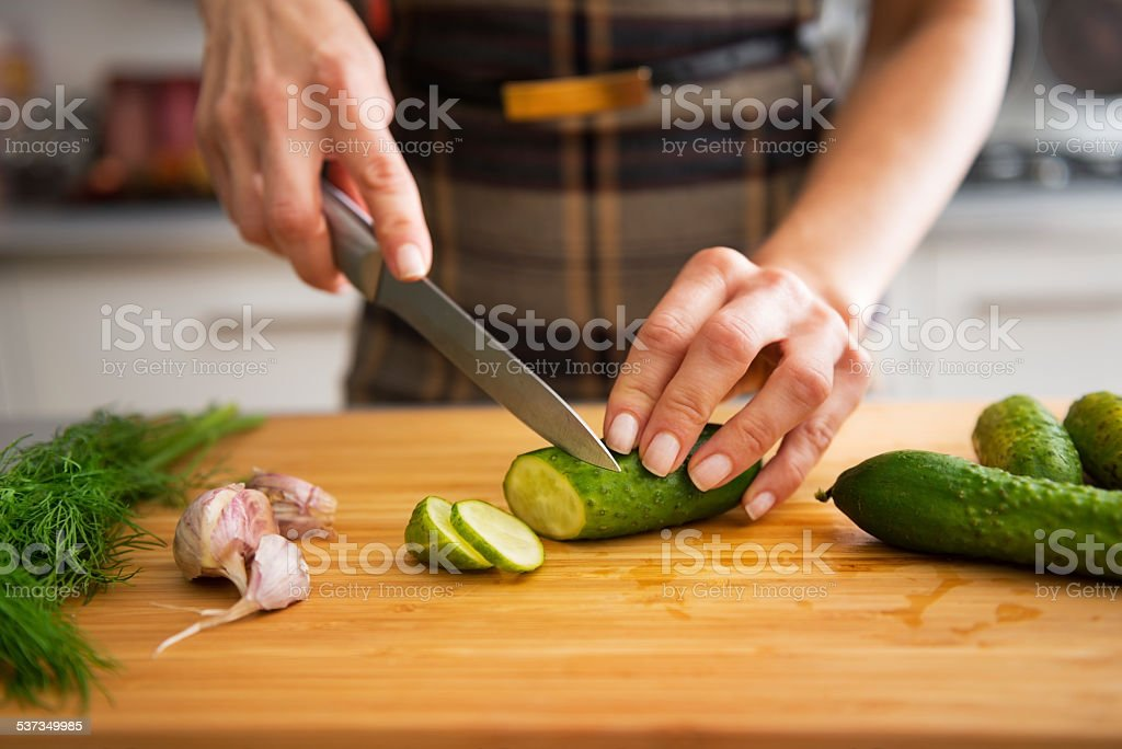 closeup on young housewife cutting cucumber for pickling in kitchen stock photo