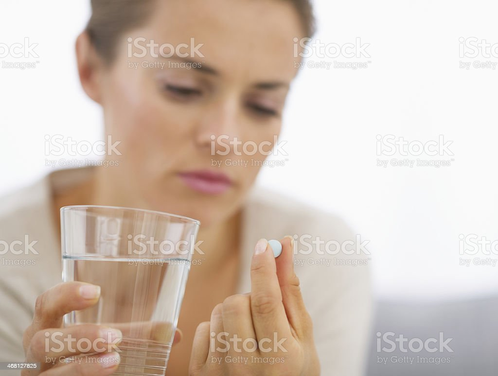 closeup on young housewife eating pills stock photo