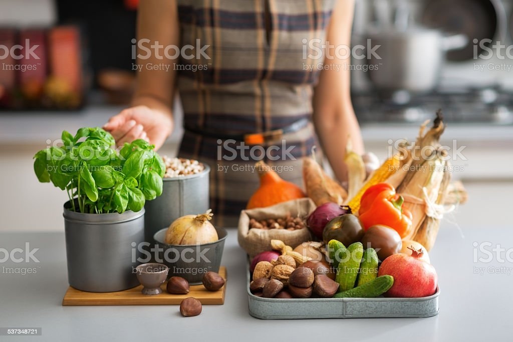 closeup on young housewife with vegetables in kitchen stock photo