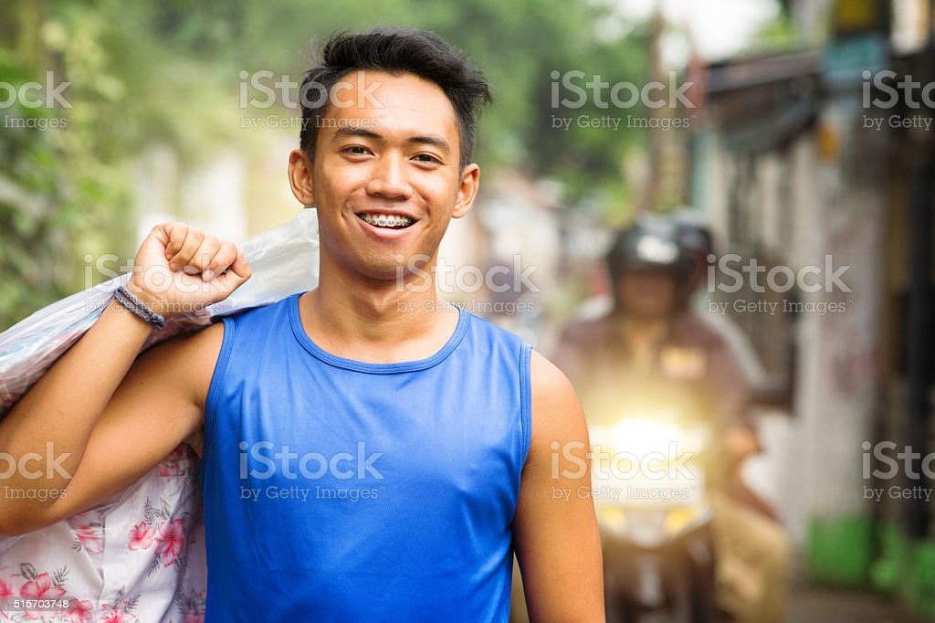 Close-up on young Indonesian man carrying dry cleaning stock photo