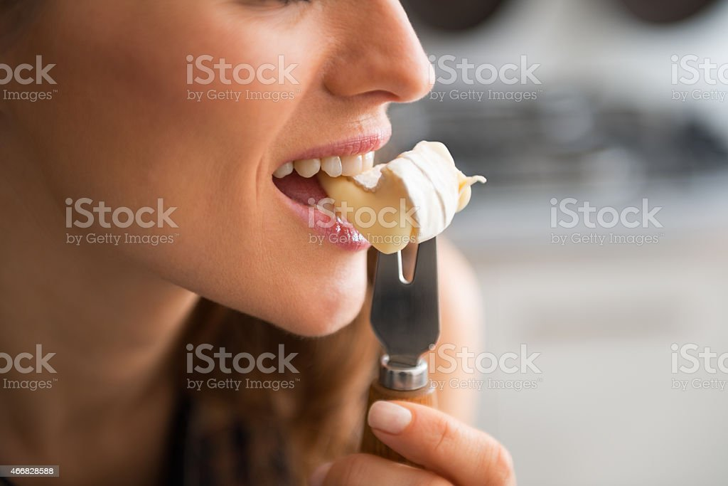 closeup on young woman eating camembert stock photo