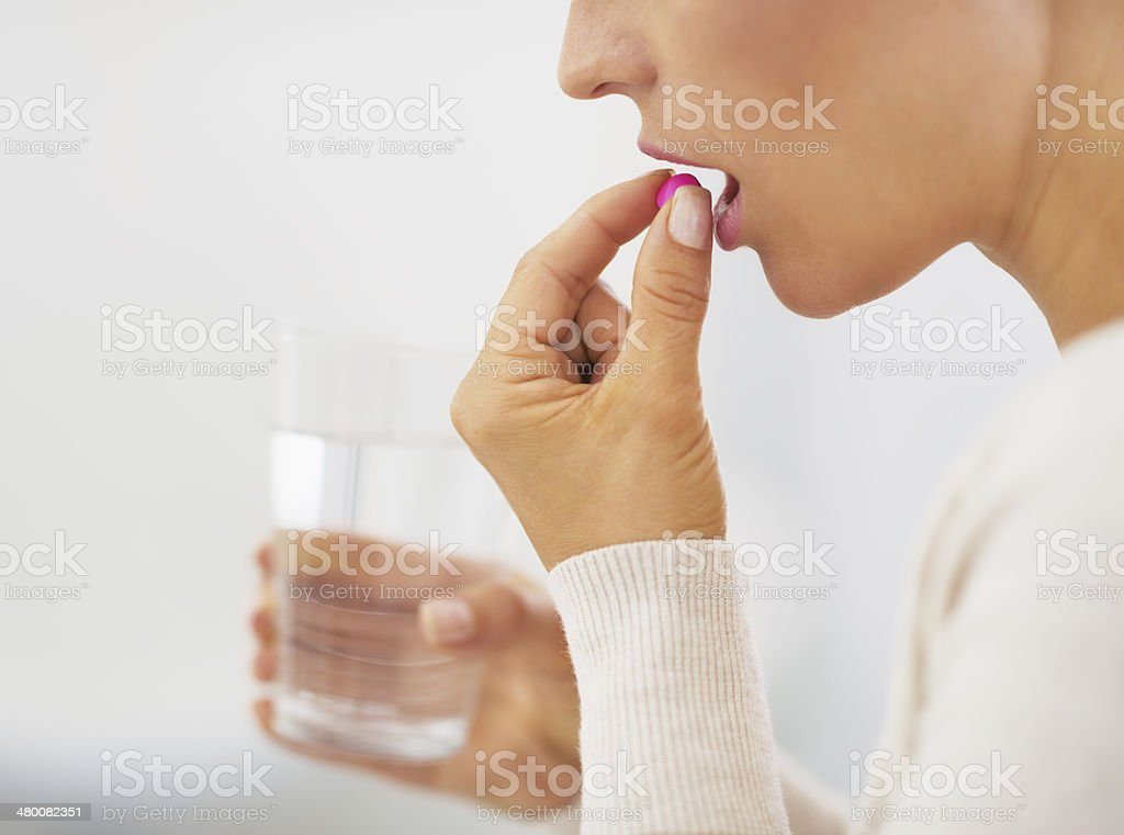 closeup on young woman eating pill stock photo