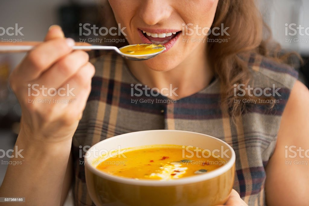 closeup on young woman eating pumpkin soup in kitchen stock photo