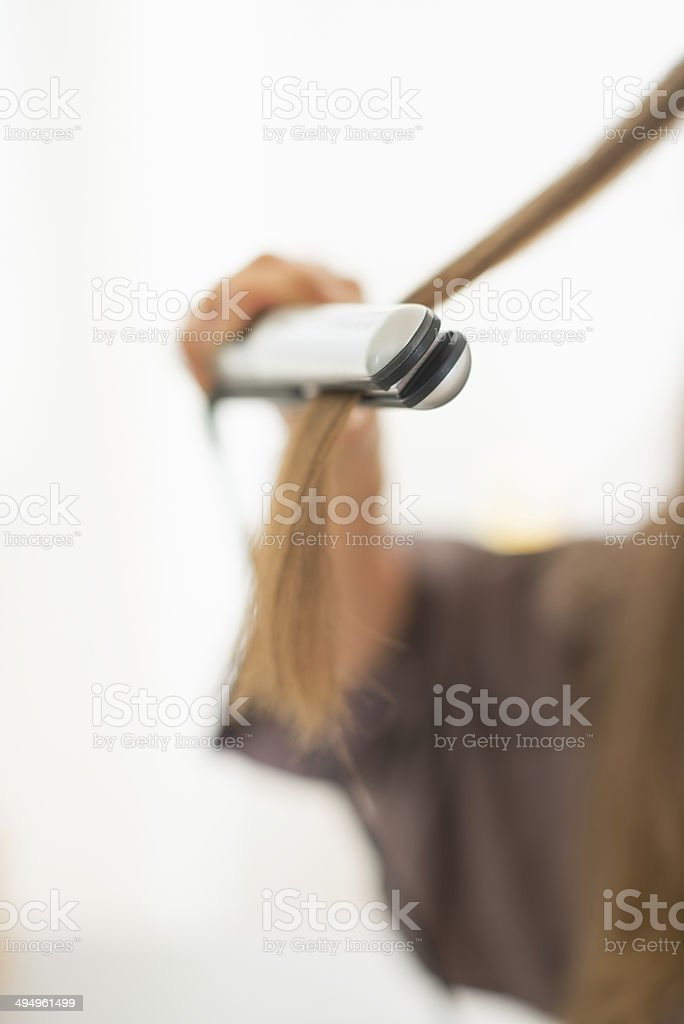 closeup on young woman using hair straightener stock photo