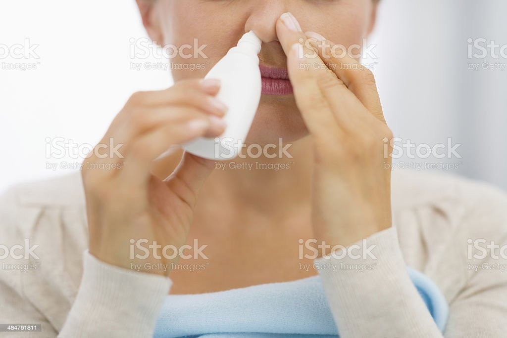 closeup on young woman using nose drops stock photo