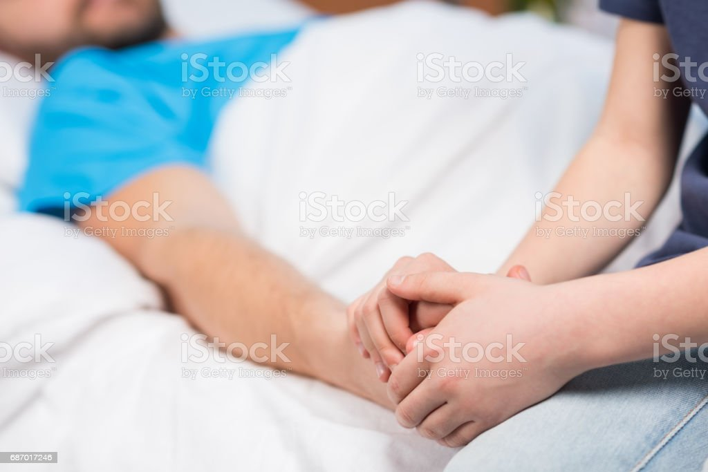Close-up partial view of son holding hand of sick father lying in hospital bed, dad and son in hospital stock photo