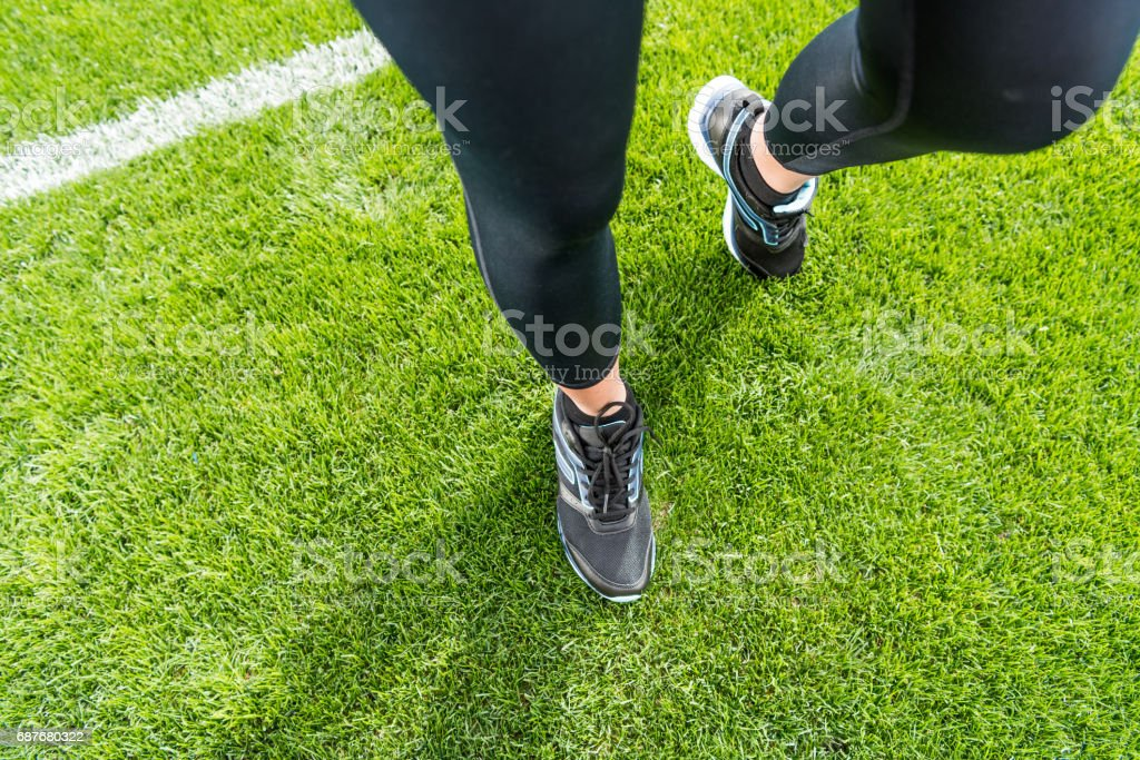 Close-up partial view of sportswoman standing on soccer stadium grass stock photo