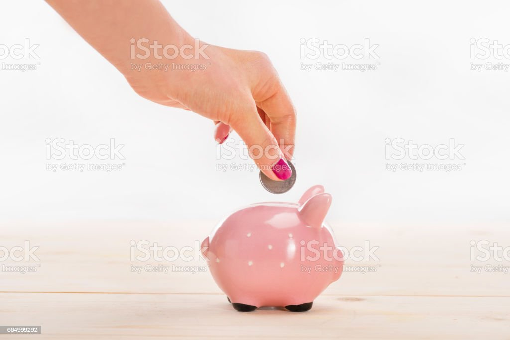 Close-up partial view of woman putting coin in piggy bank stock photo