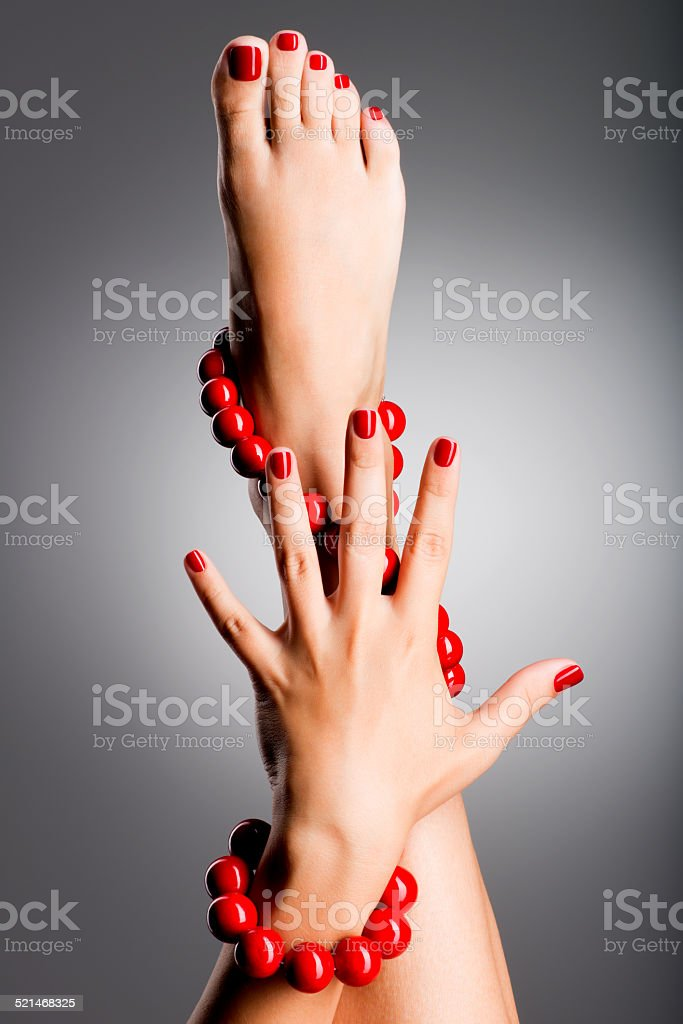 Closeup photo of a beautiful female feet with red pedicure stock photo