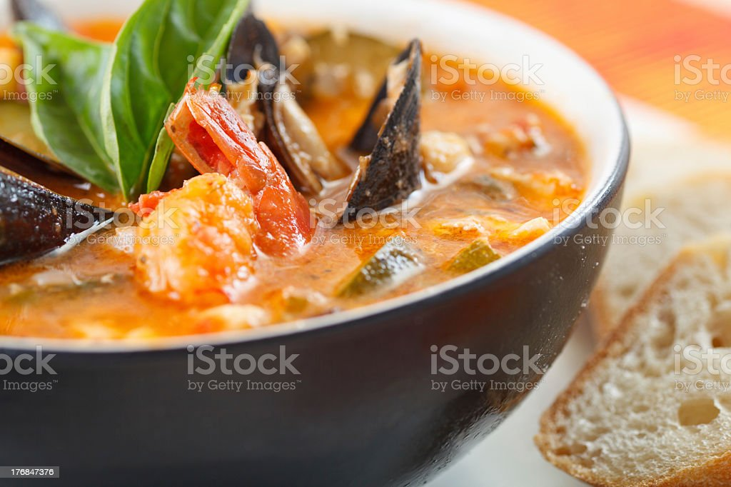Close-up photo of a bowl of mussel, shrimp and scallop soup stock photo