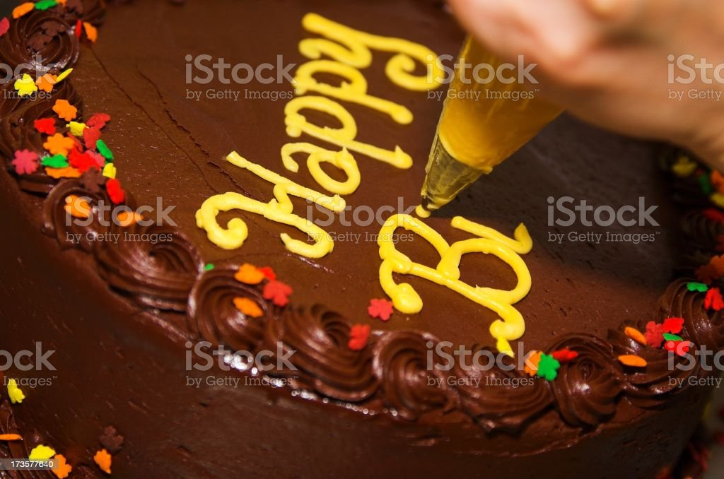 Close-up photo of a decorator writing letters on a cake royalty-free stock photo