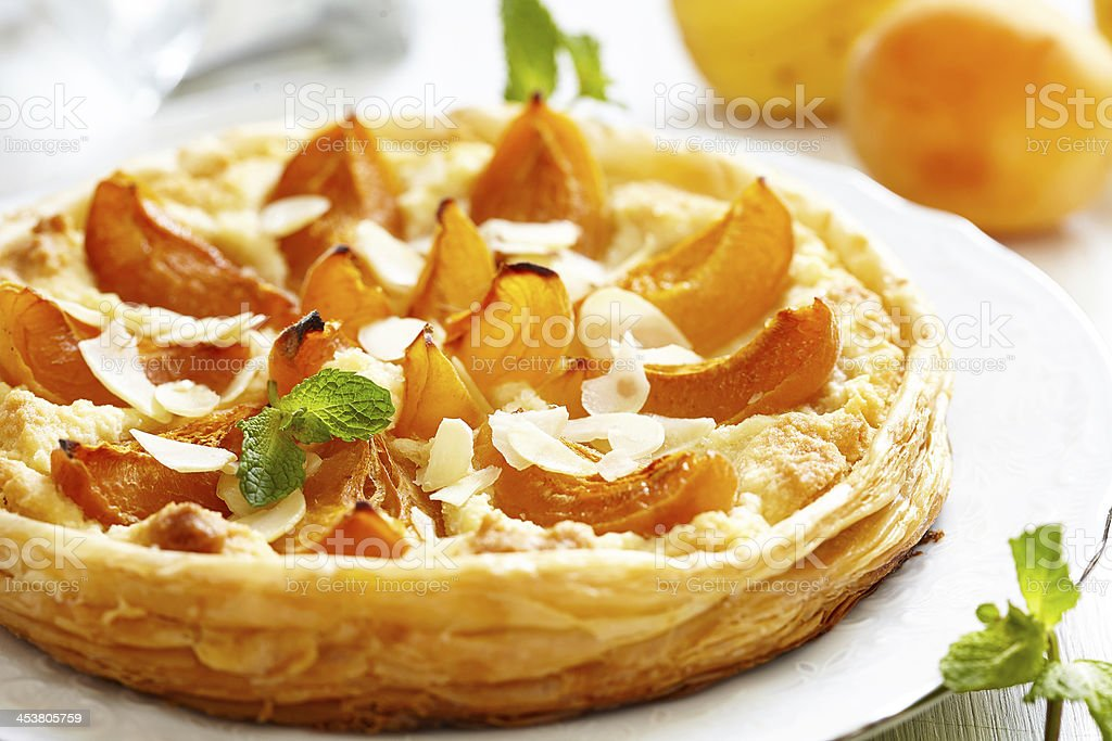 Close-up photo of an apricot and almond tart on white plate stock photo