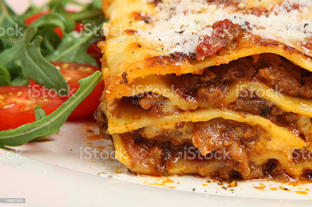 Close-up photo of baked lasagna al forno with side salad royalty-free stock photo