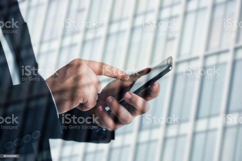 Closeup photo of businessman hands touching screen smartphone. blurred background. stock photo