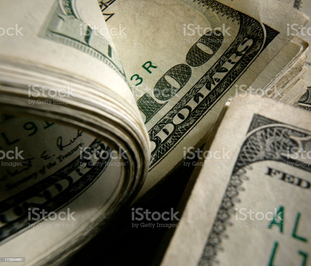 Closeup photo of curled and flat $100 bills stock photo