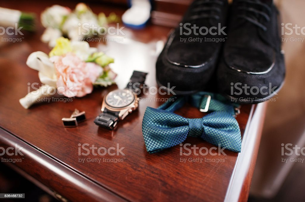 Close-up photo of groom's wedding shoes, bow tie, watch, cufflinks and buttonhole flowers. stock photo
