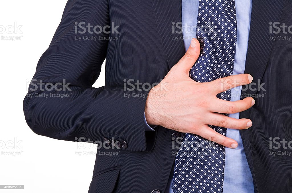Closeup photo of man in a suit clutching his heartburn stock photo