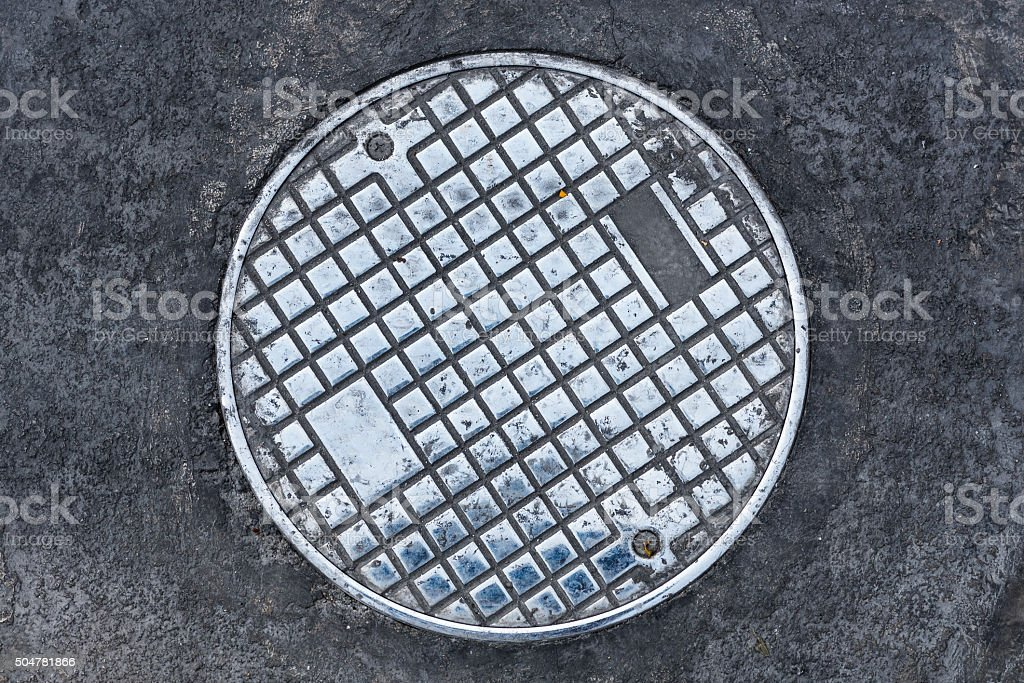 Closeup photo of Old Sewer manhole cover stock photo