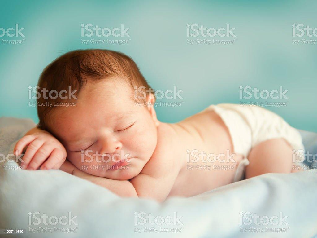 Close-up photo of sleeping newborn wearing diaper stock photo