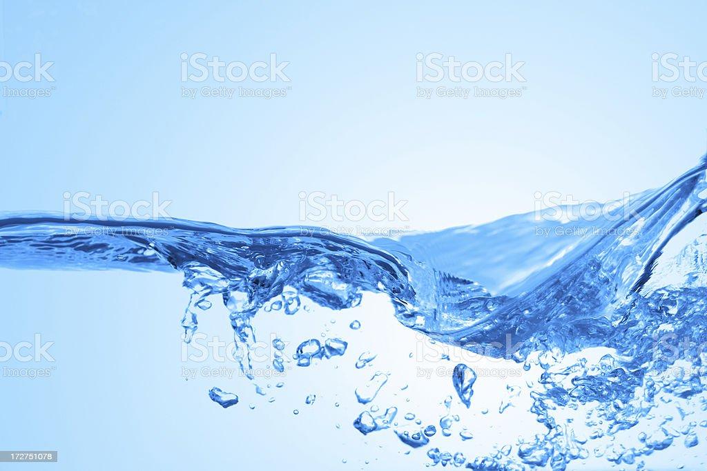 Close-up photo of splashing water on a blue background royalty-free stock photo