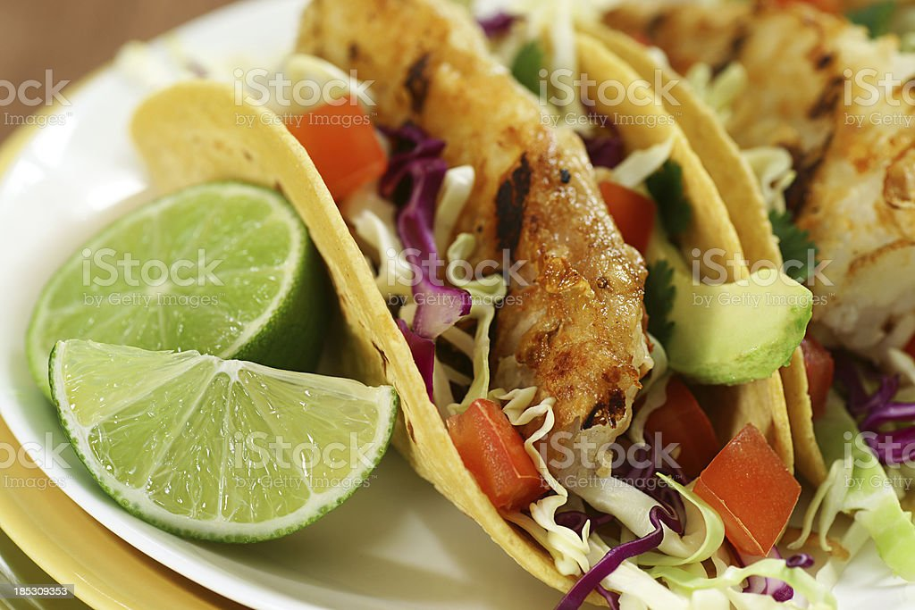 A close-up photograph of fish tacos, served with fresh lime stock photo