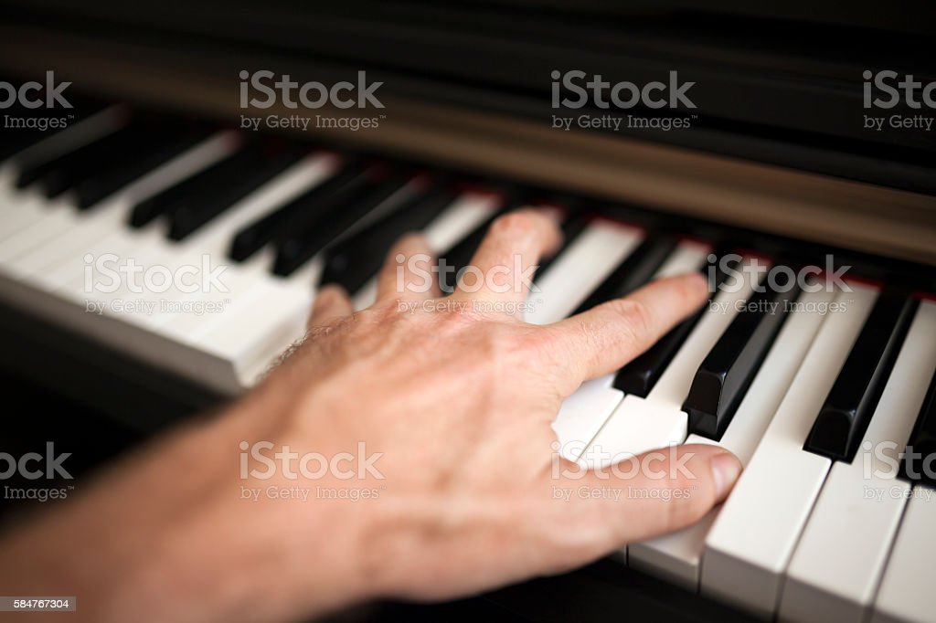 Close-up pianist hand on piano stock photo