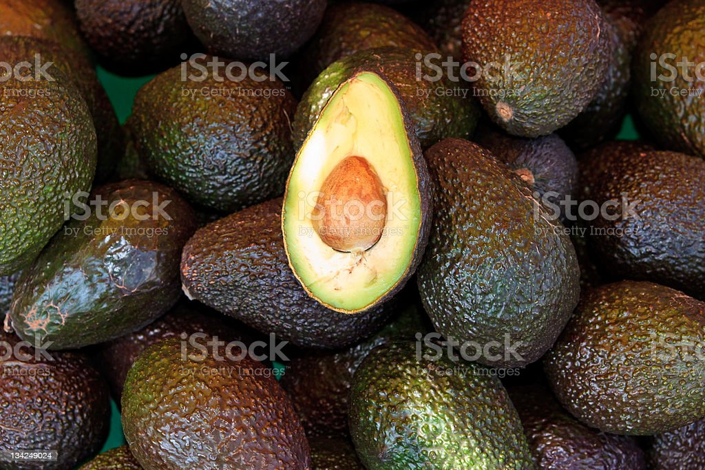 Close-up pile of fresh avocados with one sliced open stock photo