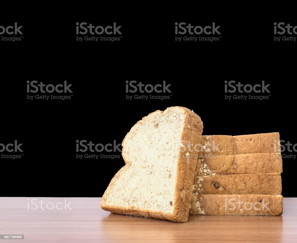 Closeup pile of wheat bread for breakfast on brown wood desk isolated on black background stock photo