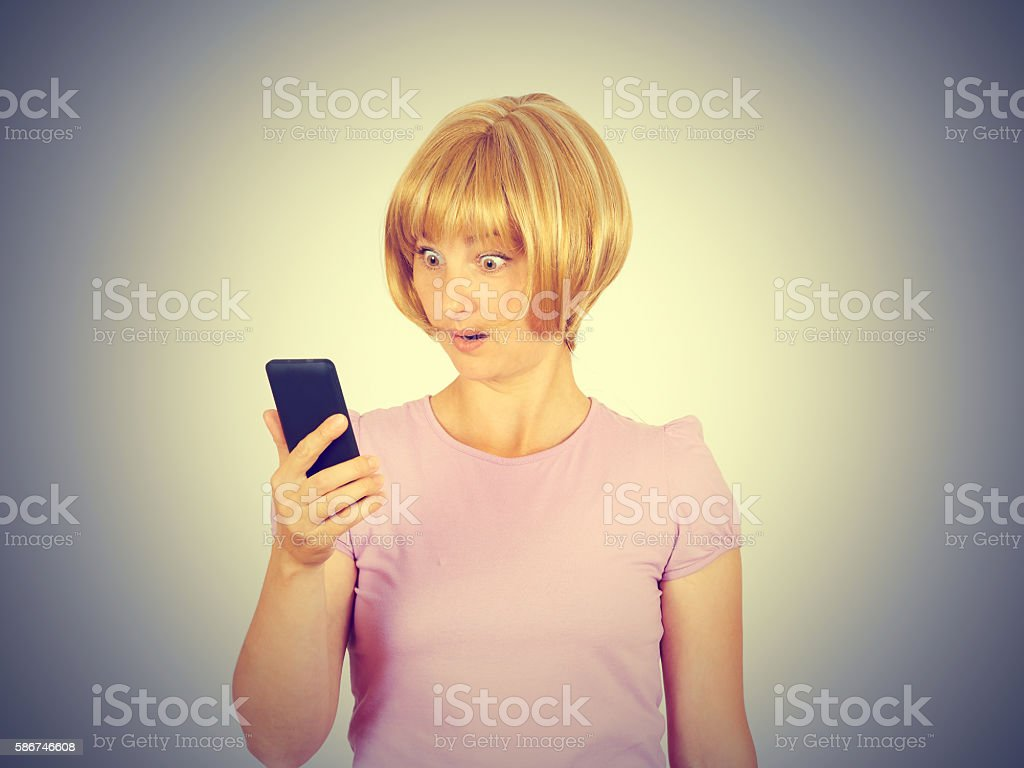 Closeup portrait anxious  young woman looking at phone seeing ba stock photo
