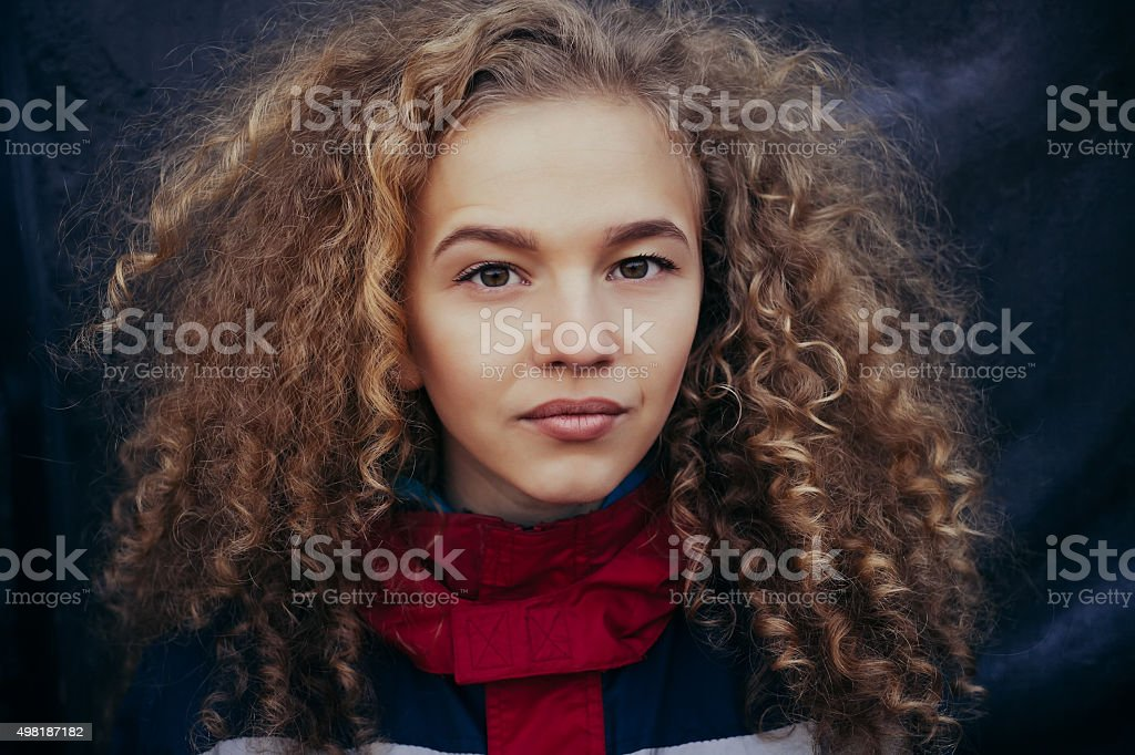 Close-up portrait beautiful model curly blond hair black background stock photo